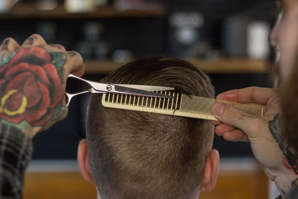 hombre con mano tatuada corta el pelo a otro hombre con tijera y peine