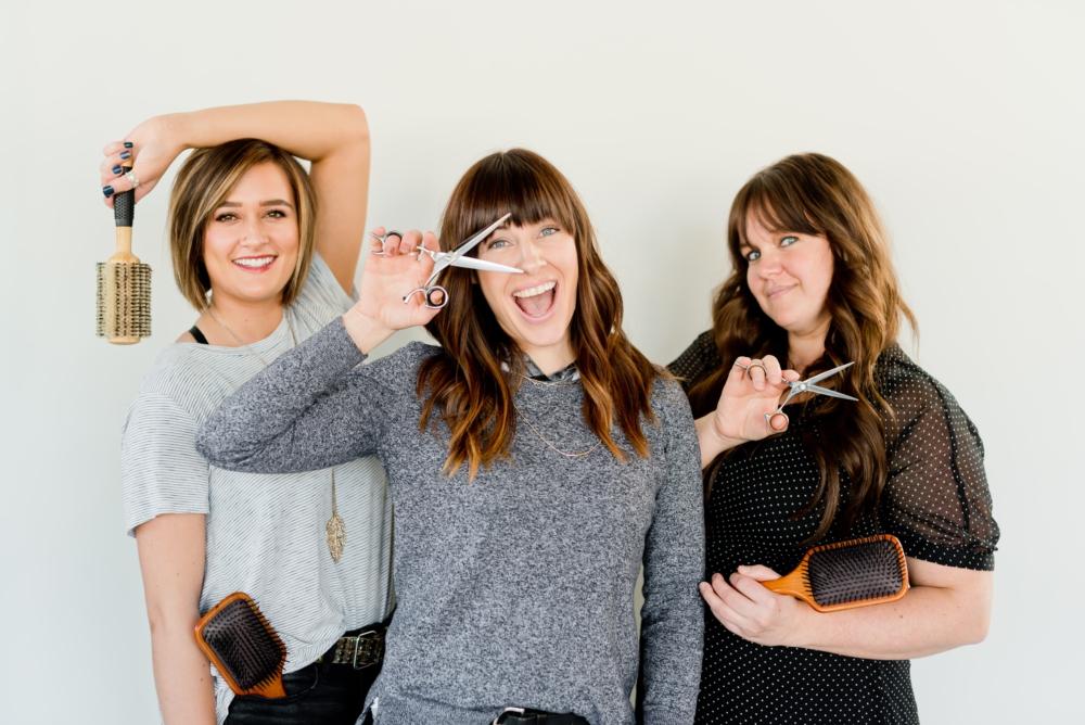 tendencias de corte y color 2021 tres mujeres peluqueras sonriendo con tijeras y cepillos en la mano