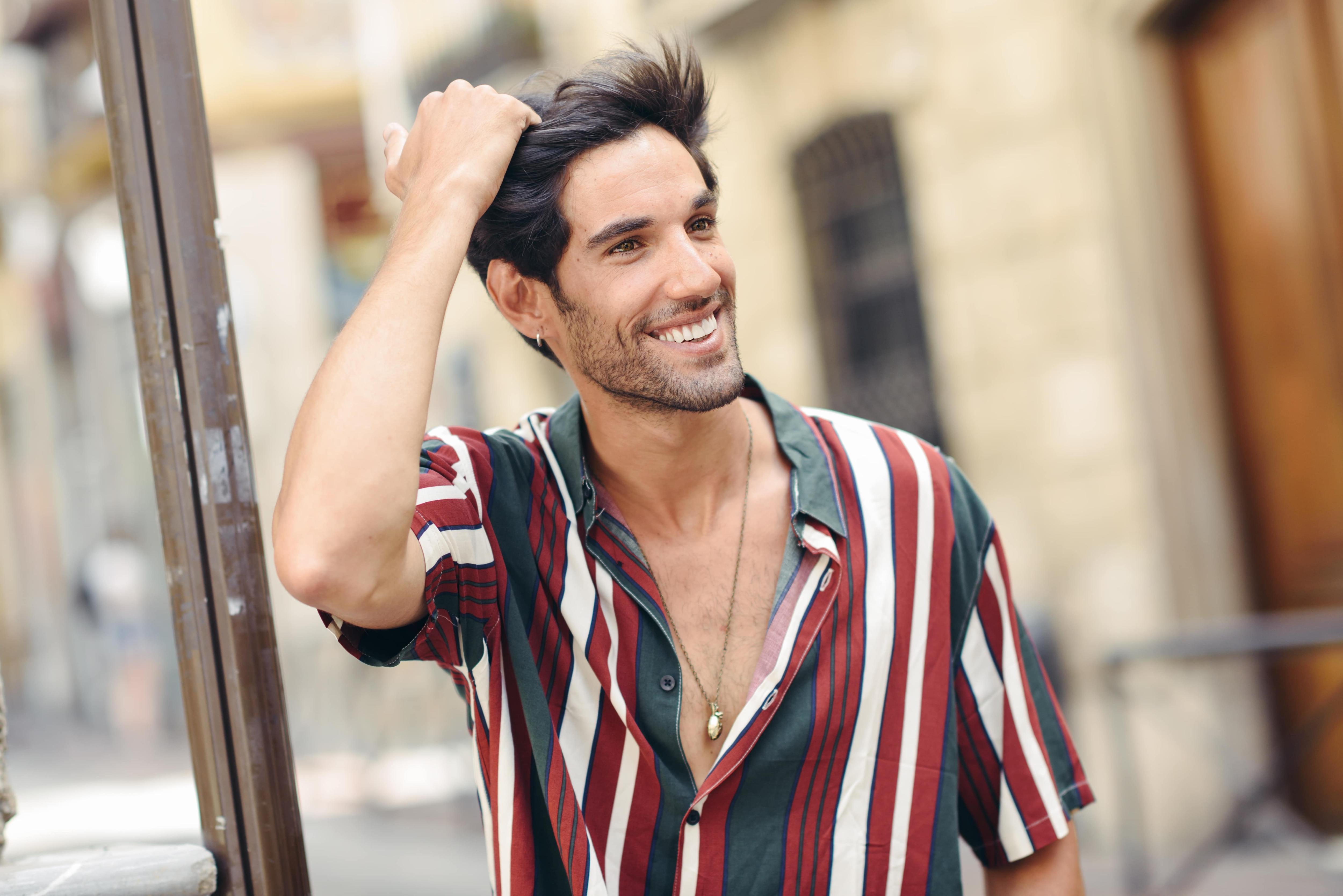 chico sonriente tocandose el pelo vistiendo camisa de rayar alopecia caida del pelo hombres