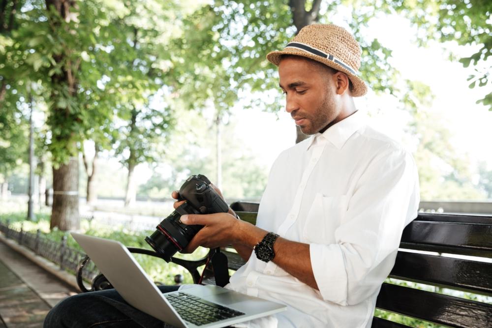 hombre con ordenador y cámara periodista en el parque
