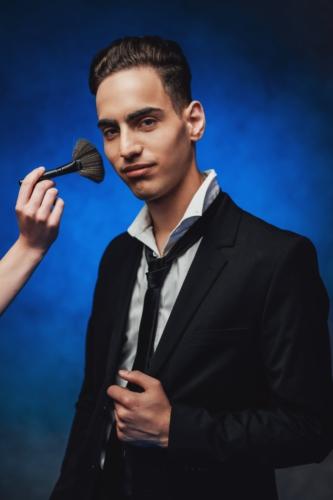 maquillaje para hombres hombre vestido de chaqueta siendo maquillado