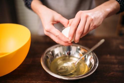manos de mujer rompiendo un huevo en un bowl